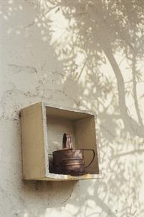 壁に掛かった棚と錆びたジョウロの写真素材 [FYI03850940]