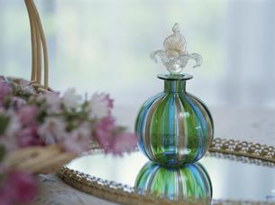 鏡の上の香水瓶と花の写真素材 [FYI03851032]