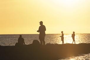 夕焼けの岩場で釣りをする人物のシルエット オアフ島 ハワイの写真素材 [FYI03852012]
