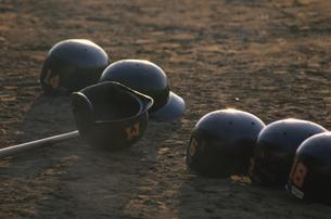 夕方の野球場に並べられたヘルメットの写真素材 [FYI03852931]