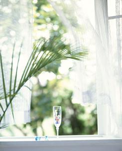 カーテンのかかった窓辺に置かれたグラスとビー玉の写真素材 [FYI03853119]