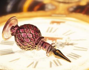 時計の上の倒れた香水瓶の写真素材 [FYI03853234]