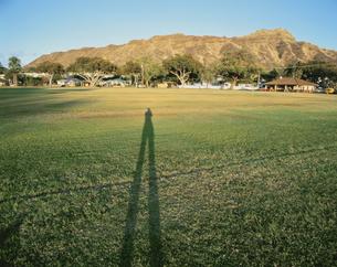 ダイヤモンドヘッドと草原に伸びる人物の影 オアフ島 ハワイの写真素材 [FYI03853252]