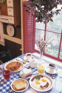 朝食が並べられた窓辺のテーブルの写真素材 [FYI03853965]