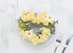 皿に載せた黄色い花のハート型のリースの写真素材 [FYI03854133]