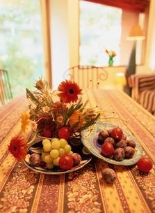 テーブルの上の花(ガーベラ)と果物の写真素材 [FYI03855319]