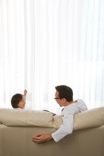 ソファーに座る父親と娘の写真素材 [FYI03855458]