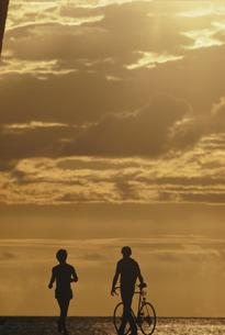 マラソンとサイクリングするカップルの後姿シルエットの写真素材 [FYI03856260]
