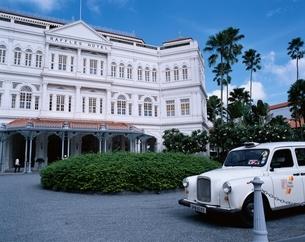 ラッフルズホテルとロンドン型タクシー   シンガポールの写真素材 [FYI03856755]