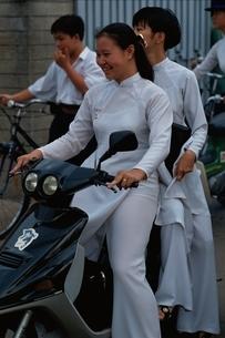 バイクに2人乗りをする民族衣装の女性 ホーチミン ベトナムの写真素材 [FYI03857462]