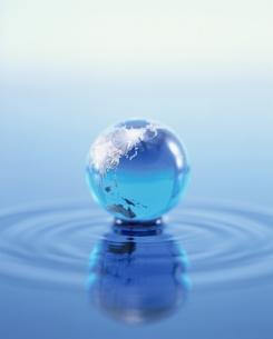 水面の波紋とガラスで作られた地球儀の写真素材 [FYI03858699]