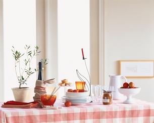 赤と白のクロスのかかったテーブルに食器の写真素材 [FYI03858701]