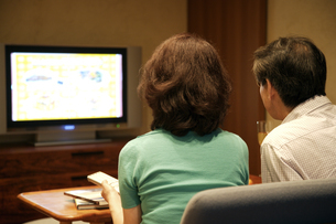 プラズマテレビを見る熟年夫婦の写真素材 [FYI03858961]