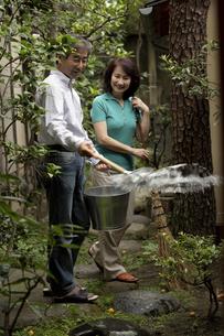 自宅の庭を掃除する熟年夫婦の写真素材 [FYI03858970]