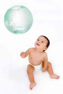 ガラスの地球儀と裸の赤ちゃんの写真素材 [FYI03859420]