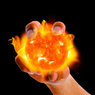 燃える球を持つ手の写真素材 [FYI03859561]