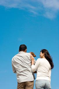 青空と犬を抱く後姿の夫婦の写真素材 [FYI03859932]