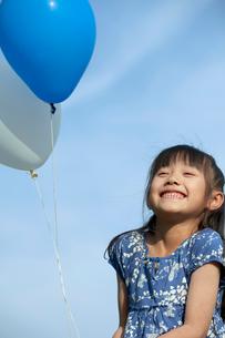 青空と風船を持つ女の子の写真素材 [FYI03860512]