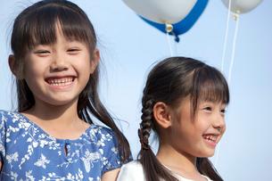 青空と風船を持つ姉妹の写真素材 [FYI03860513]