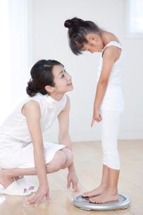 体重計に乗る娘と母の写真素材 [FYI03860562]