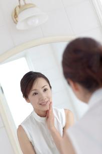 鏡を見る女性の写真素材 [FYI03860572]