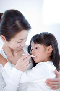 娘の熱を計る母親の写真素材 [FYI03860582]