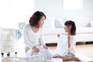 洗濯物を片づける母と娘の写真素材 [FYI03860596]