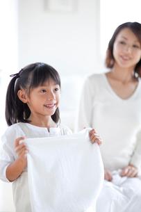 洗濯物を片づける母と娘の写真素材 [FYI03860597]