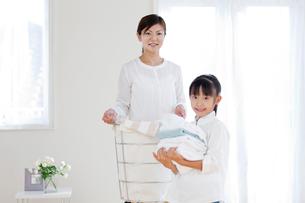 洗濯物を片づける母と娘の写真素材 [FYI03860624]