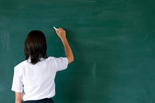 黒板に文字を書く女子高校生の写真素材 [FYI03860696]