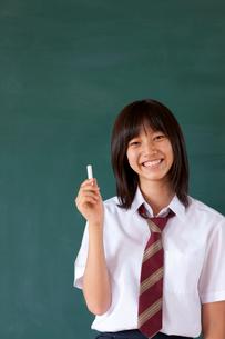 黒板の前に立つ日本人の女子高校生の写真素材 [FYI03860698]