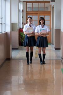 廊下で教科書を持つ二人の女子高校生の写真素材 [FYI03860699]