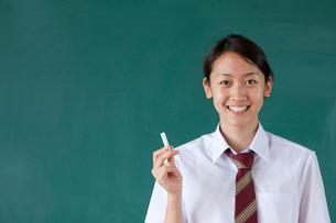 黒板の前に立つ日本人の女子高校生の写真素材 [FYI03860700]