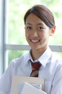 廊下で教科書を持つ女子高校生の写真素材 [FYI03860709]