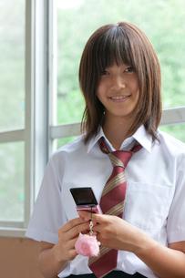 廊下で携帯電話を使う女子高校生の写真素材 [FYI03860717]
