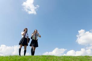 土手に立つ二人の女子高校生の写真素材 [FYI03860735]