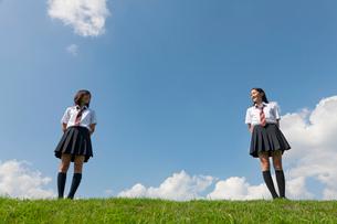 土手に立つ二人の女子高校生の写真素材 [FYI03860737]