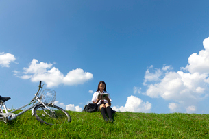 土手に座って本を読む女子高校生の写真素材 [FYI03860742]