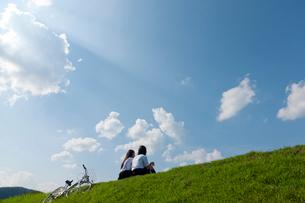 土手に座っておしゃべりする二人の女子高校生の写真素材 [FYI03860745]