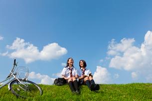 土手に座っておしゃべりする二人の女子高校生の写真素材 [FYI03860746]