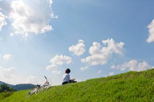 土手に座って本を読む女子高校生の写真素材 [FYI03860749]