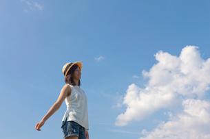 空に向かって両手を広げる帽子をかぶった10代の女の子の写真素材 [FYI03860750]