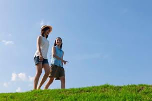 土手を歩く二人の10代の女の子の写真素材 [FYI03860752]