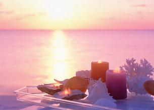 海とテーブルの上の貝殻とキャンドルの写真素材 [FYI03860847]