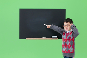 黒板を指し示す男の子の写真素材 [FYI03861141]