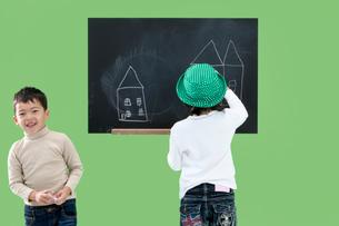 黒板に絵を描く男の子と女の子の写真素材 [FYI03861146]