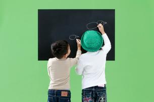 黒板に絵を描く男の子と女の子の写真素材 [FYI03861147]