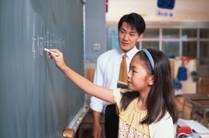 黒板で問題を解いている小学生と男性教師の写真素材 [FYI03863267]