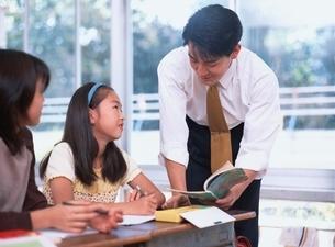 女子小学生の勉強を見上げている男性教師の写真素材 [FYI03863272]