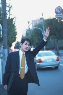 タクシーを止めようとしているビジネスマンの写真素材 [FYI03863361]